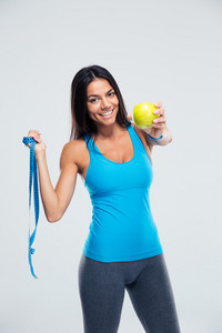 Sporty woman holding apple and measuring tape