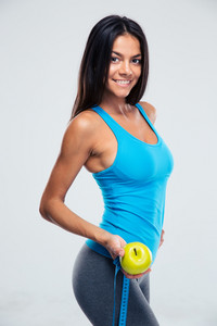 Fitness woman holding apple and measuring tape