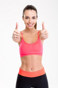Smiling joyful fitness girl showing thumbs up with both hands