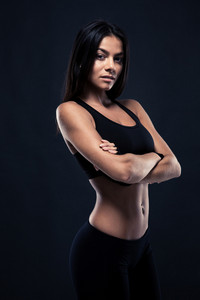 Sporty woman standing with arms folded