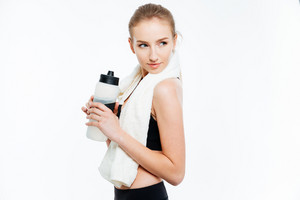 Attractive woman athlete holding bottle of water and white towel
