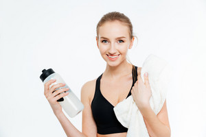 Cheerful woman athlete drinking water anf holding white towel