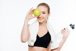 Cheerful cute young sportswoman covered eye with apple