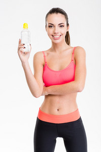 Beautiful happy fitness woman posing with a bottle of water