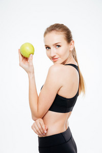 Charming woman athlete standing and posing with apple