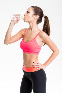 Profile of attractive young sportswoman drinking water