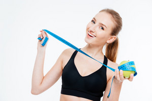Cheerful attractive sportswoman holding apple with measuring tape