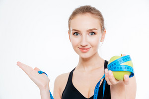 Sportswoman holding apple with measuring tape and  copyspace on palm