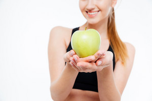 Fresh green apple held by cheerful woman athlete