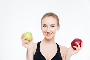 Happy beautiful sportswoman holding green and red apples