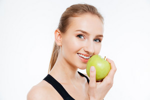Cheerful woman athlete eating an apple