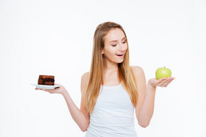 Cheerful woman choosing between healthy and unhealthy food