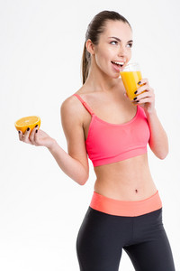Cheerful fitness girl drinking  juice and holding half of orange