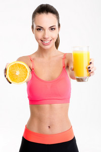 Beautiful  fitness woman giving a juice and half of orange