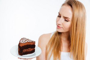 Pensive beautiful woman looking at piece of chocolate cake