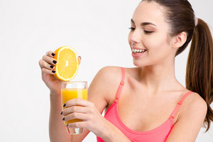 Attractive sportswoman in pink top squeezing orange making fresh juice