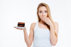 Beautiful confused woman on diet holding piece of chocolate cake