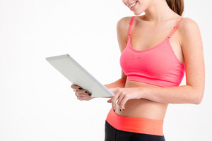 Tablet used by slim beautiful young sportswoman