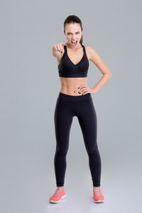 Mad angry fitness woman screaming and pointing on you