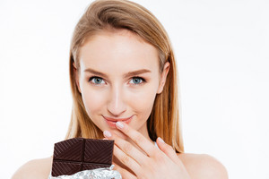 Beautiful smiling young woman eating bar of chocolate