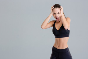 Crazy hysterical shouting fitness girl in black top and leggings