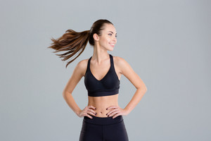 Positive cheerful fitness woman warming up and turning her head