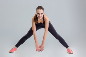 Cheerful attractive young fitness woman doing exercises and looking camera