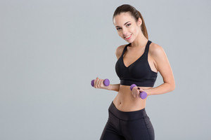 Beautiful happy fitness girl holding dumbbells isolated over grey background
