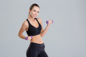 Cheerful attractive young sportswoman lifting dumbbells