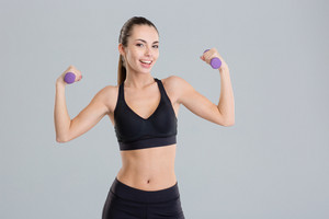 Happy beautiful young fitness woman working out with dumbbells