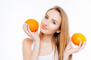 Attractive smiling woman posing with two fresh oranges