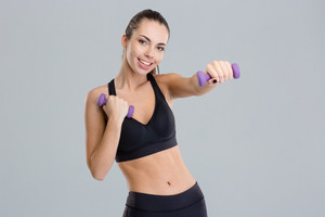 Positive pretty fitness girl exercising with dumbbells