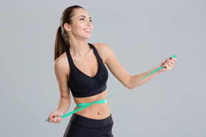 Portrait of excited happy young fitness woman with measuring tape