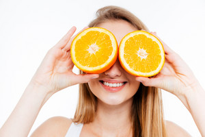 Funny cheerful woman holding two halves of orange agains eyes