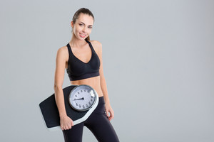 Beautiful smiling young fitness woman in tracksuit holding weigh scale