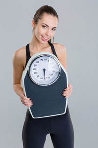Portrait of happy fitness girl in sportwear with weigh scale