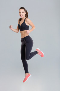 Cheerful active young sportswoman in fitness wear running