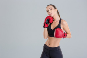 Confident pretty fitness girl posing in red boxing gloves