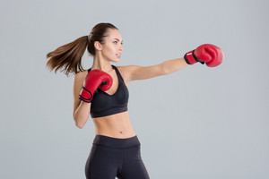 Profile of beautiful young boxing sportswoman in red gloves