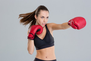 Closeup of young fitness woman boxing using red gloves