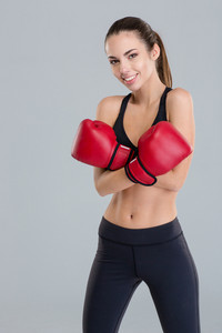 Attractive fitness girl in red boxing gloves with crossed arms