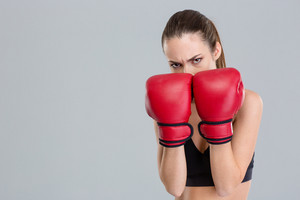 Strong intense fitness woman covered her face with boxing gloves