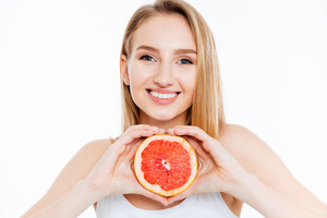 Woman holding slice of grapefruit