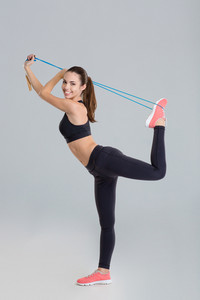 Active positive young fitness woman stretching with jumping rope
