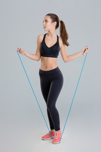 Thoughtful pretty fitness girl training with jumping rope