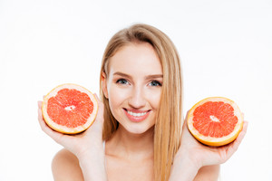 Happy woman holding grapefruit