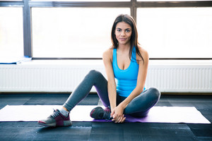 Thoughtful fit woman sitting on yoga mat