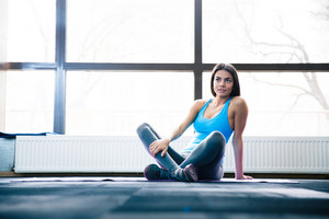 Pensive woman sitting on yoga mat