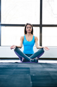 Beautiful woman meditating at gym