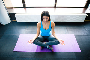 Young woman meditating at gym